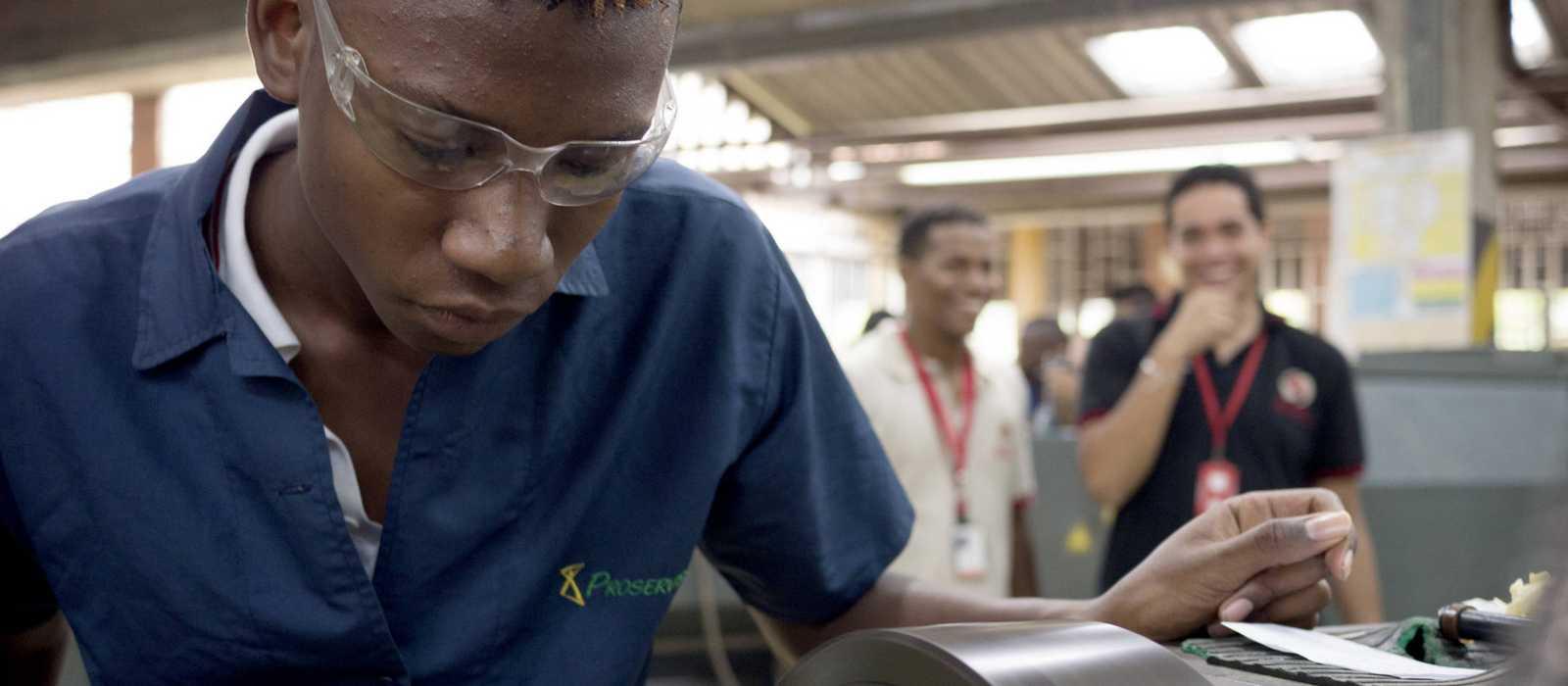 Jugendlicher mit blauem Overall in einer Auto-Werkstatt