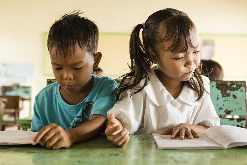 Kleiner Junge und Mädchen sitzen auf einer Schulbank und lesen